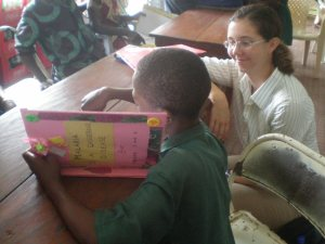 Kid and Katie M reading book on malaria, made by teachers at Bo FoSL Teacher Training 5
